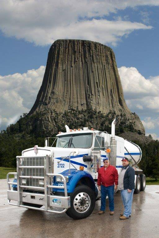 Dixon Bros and a fleet vehicle in fron t of Devil's Tower, WY.